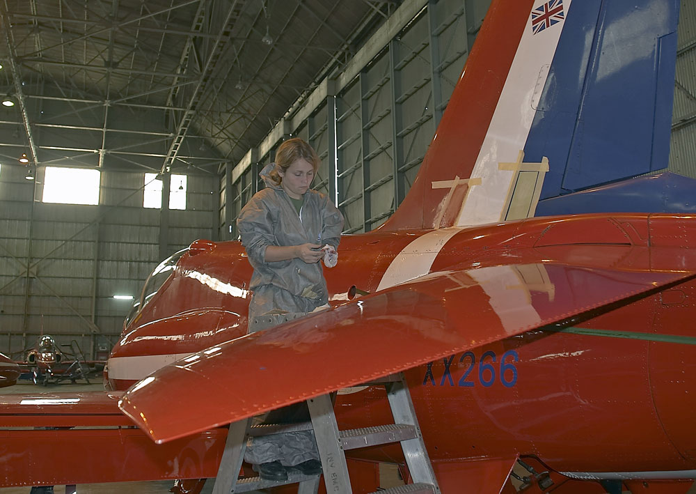 Taking great pride in her work this painter prepares another jet for the team